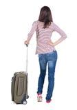 Opinión trasera la mujer que camina con la maleta Fotografía de archivo