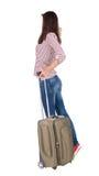 Opinión trasera la mujer que camina con la maleta Imagen de archivo