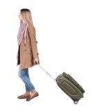 Opinión trasera la mujer que camina con la maleta muchacha hermosa en el MES Fotografía de archivo libre de regalías