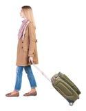 Opinión trasera la mujer que camina con la maleta muchacha hermosa en el MES Imagenes de archivo