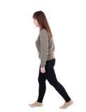 Opinión trasera la mujer que camina muchacha rubia hermosa en el movimiento Imagen de archivo libre de regalías