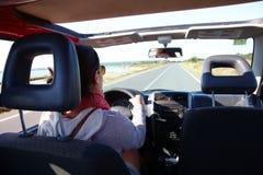 Opinión trasera la mujer que conduce el coche por la playa Fotos de archivo