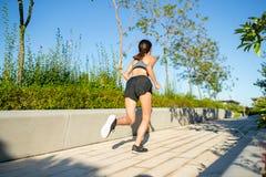 Opinión trasera la mujer que corre en parque Imagen de archivo