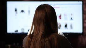 Opinión trasera la mujer que hace compras en línea con el ordenador metrajes