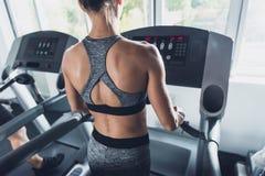 opinión trasera la mujer que hace ejercicios cardiios en la rueda de ardilla Imagenes de archivo