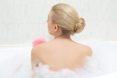 Opinión trasera la mujer que se relaja en baño y que se lava Imagenes de archivo