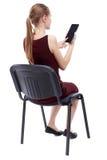 Opinión trasera la mujer que se sienta en silla y miradas en la pantalla Fotos de archivo