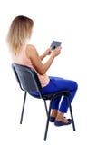Opinión trasera la mujer que se sienta en silla y miradas en la pantalla Imagenes de archivo