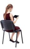 Opinión trasera la mujer que se sienta en silla y miradas en la pantalla Fotografía de archivo