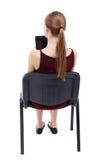 Opinión trasera la mujer que se sienta en silla y miradas en la pantalla Fotos de archivo libres de regalías