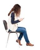 Opinión trasera la mujer que se sienta en silla y miradas en la pantalla de t Imágenes de archivo libres de regalías