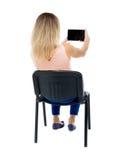 Opinión trasera la mujer que se sienta en silla y miradas en la pantalla de t Imagen de archivo