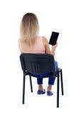 Opinión trasera la mujer que se sienta en silla y miradas en la pantalla de t Fotos de archivo libres de regalías