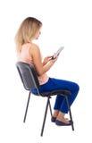 Opinión trasera la mujer que se sienta en silla y miradas en la pantalla de t Fotos de archivo