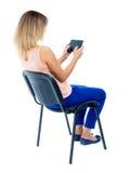 Opinión trasera la mujer que se sienta en silla y miradas en la pantalla de t Foto de archivo libre de regalías