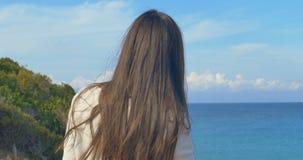 Opinión trasera la mujer que toca su pelo Agua azul soleada de la costa y del claro metrajes