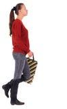 Opinión trasera la mujer que va con los bolsos de compras. Imagen de archivo