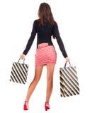 Opinión trasera la mujer que va en mujer del vestido con los bolsos de compras Imágenes de archivo libres de regalías