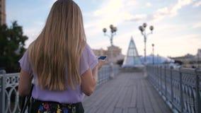 Opinión trasera la mujer rubia que camina con el teléfono móvil metrajes