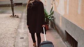Opinión trasera la mujer turística en negro Opinión del primer de las piernas femeninas que caminan con una maleta en la calle metrajes
