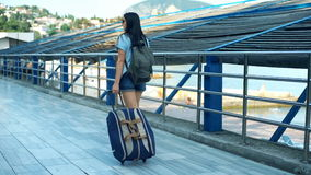 Opinión trasera la mujer turística que camina con la maleta y la mochila almacen de metraje de vídeo
