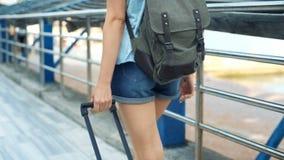 Opinión trasera la mujer turística que camina con la maleta y la mochila almacen de video