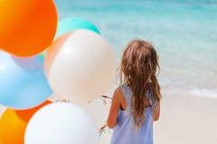 Opinión trasera la niña con los globos en la playa Imagen de archivo libre de regalías
