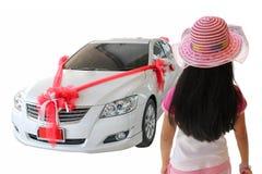 Opinión trasera la niña que mira el nuevo coche con el arco rojo como pres Fotos de archivo libres de regalías