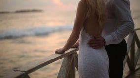 Opinión trasera la novia y el novio que disfrutan de puesta del sol en la playa tropical cerca de la barandilla el vacaciones Rec metrajes