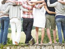 Opinión trasera los amigos que se colocan en la pared de piedra Foto de archivo