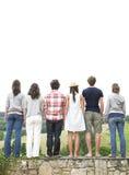 Opinión trasera los amigos que se colocan en la pared de piedra Imágenes de archivo libres de regalías