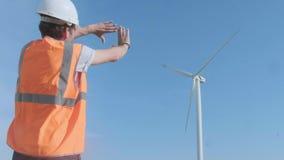 Opinión trasera los ingenieros que discuten contra las turbinas en parque eólico mientras que camina a lo largo del camino el día almacen de metraje de vídeo