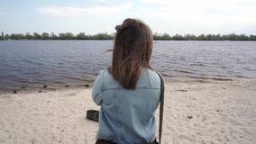 Opinión trasera media la mujer con el pelo hermoso en la orilla almacen de video