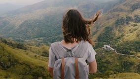 Opinión trasera media la mujer turística feliz con la mochila y el viento que soplan en el pelo que medita, Mountain View épico d almacen de video