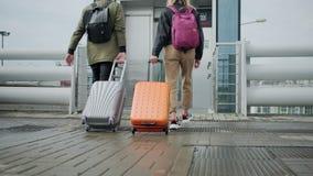 Opinión trasera pasajeros que caminan con las maletas, acercándose para levantar almacen de metraje de vídeo