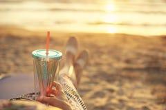 Opinión trasera sobre una mujer que disfruta de puesta del sol con el cóctel en Albania en la costa arenosa del mar adriático foto de archivo libre de regalías