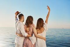 Opinión trasera tres mejores amigos que viajan por el barco que abraza y que agita mientras que mira el mar Gente que está en luj Fotos de archivo libres de regalías