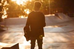 Opinión trasera un adolescente masculino africano joven con los auriculares Imagen de archivo