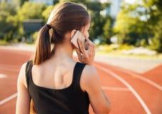 Opinión trasera un atleta de sexo femenino que habla en el teléfono móvil Foto de archivo libre de regalías