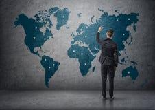Opinión trasera un hombre de negocios que hace marcas en mapa del mundo Fotos de archivo libres de regalías