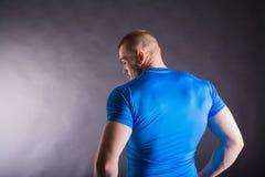 Opinión trasera un hombre joven muscular que se coloca en estudio en fondo oscuro Imágenes de archivo libres de regalías