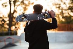Opinión trasera un individuo masculino del adolescente que sostiene el monopatín Imagenes de archivo