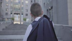 Opinión trasera un muchacho bien vestido hermoso con la chaqueta en su situación del hombro en la calle que mira el edificio seri almacen de metraje de vídeo
