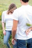 Opinión trasera un novio que oculta una flor Foto de archivo