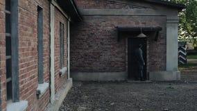Opinión trasera un soldado alemán que va a una puerta de un edificio de ladrillo rojo de un piso, golpeando en él, dando vuelta a almacen de video