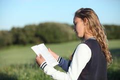 Opinión trasera una muchacha adolescente hermosa que lee un libro Fotos de archivo libres de regalías