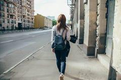 Opinión trasera una muchacha del inconformista que camina en la calle de la ciudad Imágenes de archivo libres de regalías