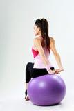 Opinión trasera una mujer joven del deporte que estira en fitball Imagen de archivo
