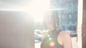 Opinión trasera una mujer joven elegante en un poco vestido negro y con los pendientes masivos que sale fuera de la oficina, vuel almacen de video