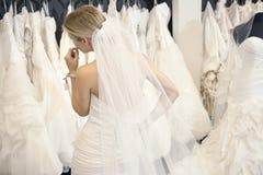 Opinión trasera una mujer joven en el vestido de boda que mira los vestidos nupciales en la exhibición en boutique Foto de archivo